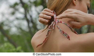 Girl tying braid around the neck close up rear - sexy girl...