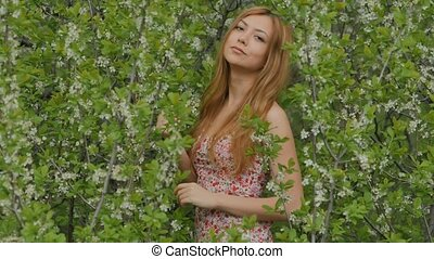 girl smiles against a background of flowering branches in spring