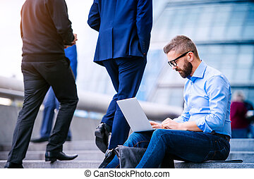 Manager with laptop, sitting on stairs, London, City Hall -...