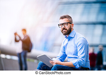 Manager with tablet, sitting on stairs, London, City Hall -...