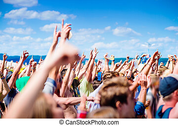 Teenagers at summer music festival clapping and singing -...