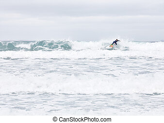 Surfer on wave - Young male surfer wearing blue wetsuit...