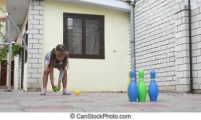 Five-year girl playing in a childrens bowling in the yard