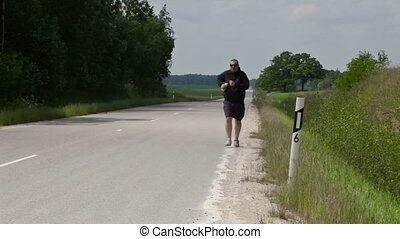 Man running along the edge of the highway