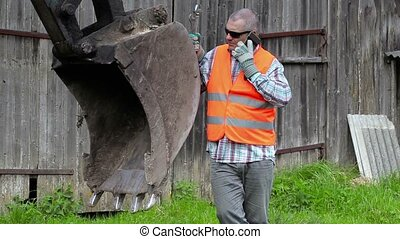 Worker talking on smart phone near tractors excavator scoop
