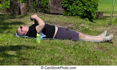 Man with overweight do exercises with dumbbells at outddor...