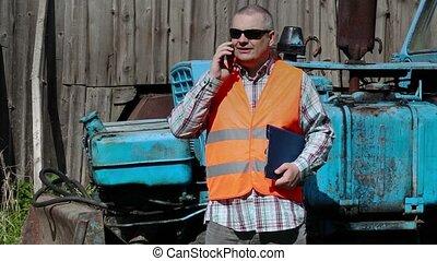 Worker talking on smart phone near tractor