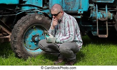 Worker looking to adjustable wrench and thinking near...