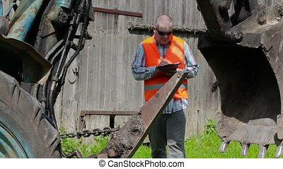 Worker checking tractor technical condition