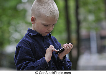 playing video games outdoor - young blonde boy playing...