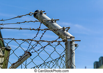 fence with barbed wire to shut off - a site is secured by a...
