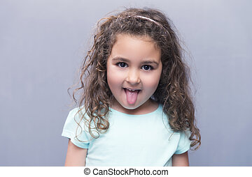 Portrait of curly-haired girl sticking out tongue - Portrait...