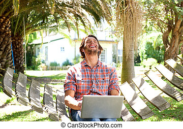 Young man laughing with laptop outdoors - Portrait of a...