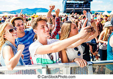 Teenagers at summer music festival in crowd taking selfie...