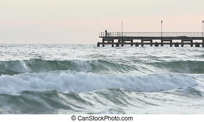 A lone fisherman is fishing on sea wharf after sunset