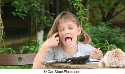 Girl sits at a table in the courtyard and grimacing showing...