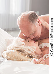 Passionate senior couple - Senior couple in love lying in...