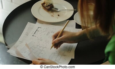 The woman is working with the blueprints, drawings sitting in the cafe. She is correcting plans of houses