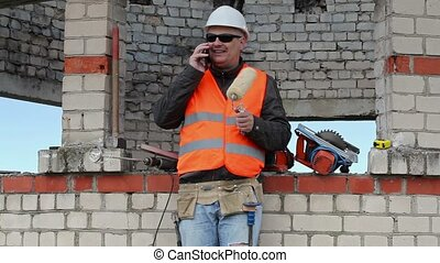 Builder with paint roller talking on smart phone