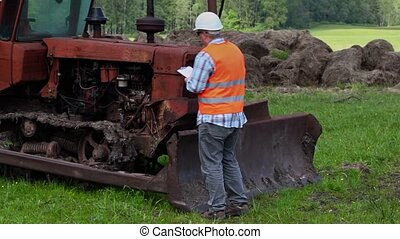 Worker writes and walking near the bulldozer