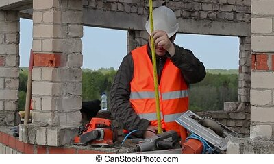 Builder using measuring tape in the unfinished building