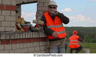 Builder drinking water near unfinished building