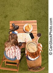 Ladies sitting at table in park - Top back vie of beautiful...