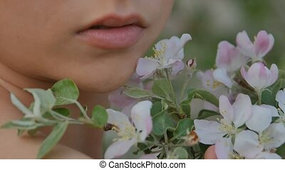 girls face close up on a background of apple-tree flowers -...