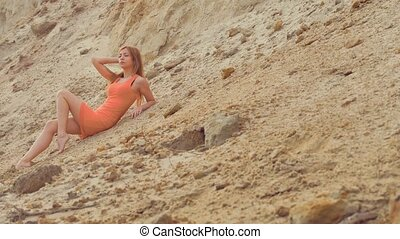 girl posing on the sandy slope sexy - blonde girl in a short...