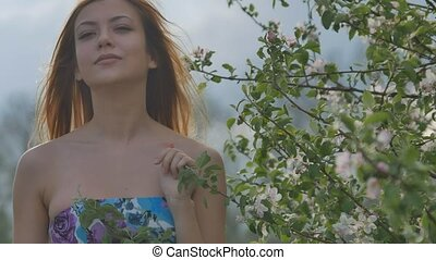 girl smiling near the blooming apple branch