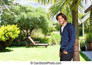 Happy young man standing against tree in backyard - Portrait...
