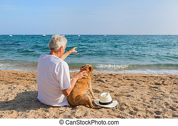 Senior man with dog at the beach - Senior man with dog in...