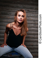 Cool contemporary young woman with long blonde hair sitting...