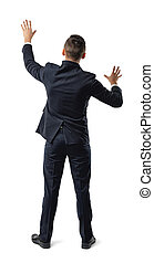 Back view of businessman touching big sensor panel or wall.