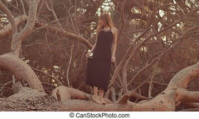 Girl walking barefoot on a tree trunk - beautiful blonde...