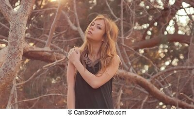 girl on a background of dry pine branches at sunset