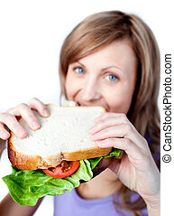 Smiling woman holding a sandwich