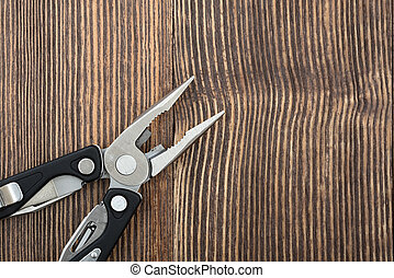 Multitool on wooden surface - Simple pliers and multitool on...