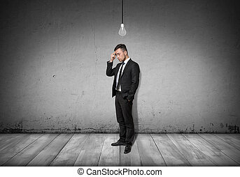 Full body of businessman stands and thinks with turned-off bulb over his head