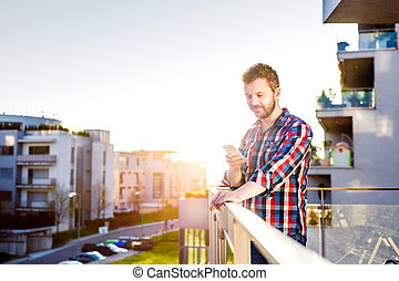 Hipster businessman with smart phone texting, standing on...