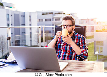 Businessman with laptop and cup of coffee, resting - Hipster...