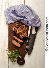 roasted beef shoulder with meat fork and knife and rosemary...