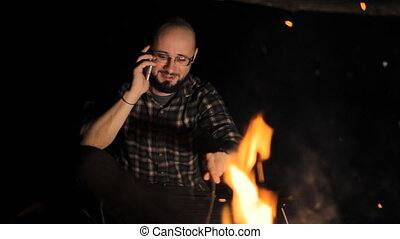 Man near campfire call with smartphone at night Talking on...