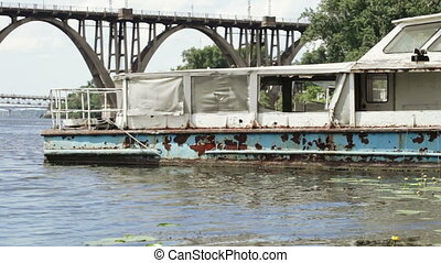Old river ship in city - In river grows Water lily yellow