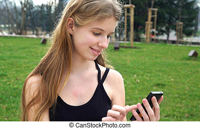 Woman using touchscreen phone outdoors in city park Woman...