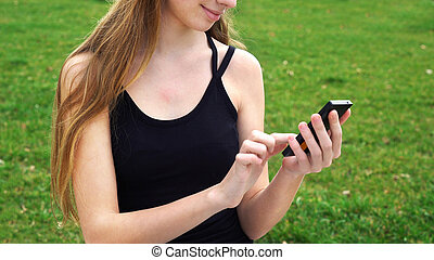 Close-up woman hands using touchscreen phone outdoors in...