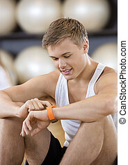 Man Using Activity Tracker While Sitting In Gym - Smiling...