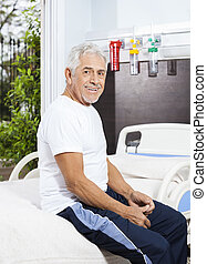 Happy Senior Man Sitting On Bed At Rehab Center - Side view...