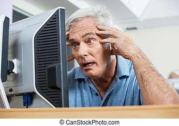 Stressed Senior Man Looking At Computer Monitor