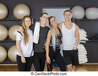 Male And Female Friends Standing Arms Around In Gym -...